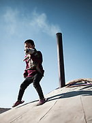 A mongolian boy walks on the roof of his yurt to pick up his stray cat. Dalanzadgab town.