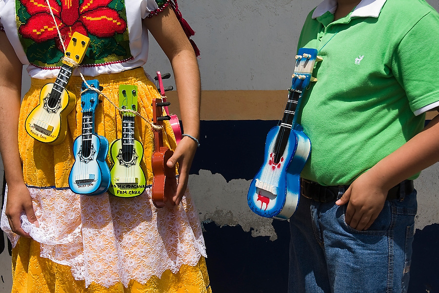 Novelty painted guitar ornaments hang from the necks of parade participants in Paracho, Michoacan state, Mexico on August 10, 2008 during the annual Feria Internacional de la Guitarra. Parades for different professions are held each day of the week-long festival, culminating in the parade of the guitar makers.
