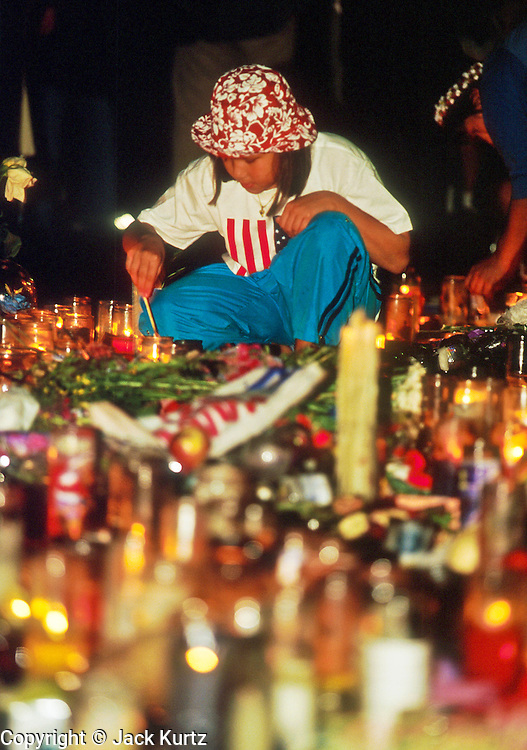 NEW YORK, NY: A girl lights a candle at a memorial for people killed in the WTC attacks in Union Square in New York City, Sept 18, 2001. Almost 3,000 people were killed when terrorists, affiliated with Osama bin Laden, hijacked and crashed two passenger jets into the twin towers on the southern tip of Manhattan. Thousands of memorials for the dead and missing have been built in lower Manhattan, many of them in Union Square. PHOTO BY JACK KURTZ
