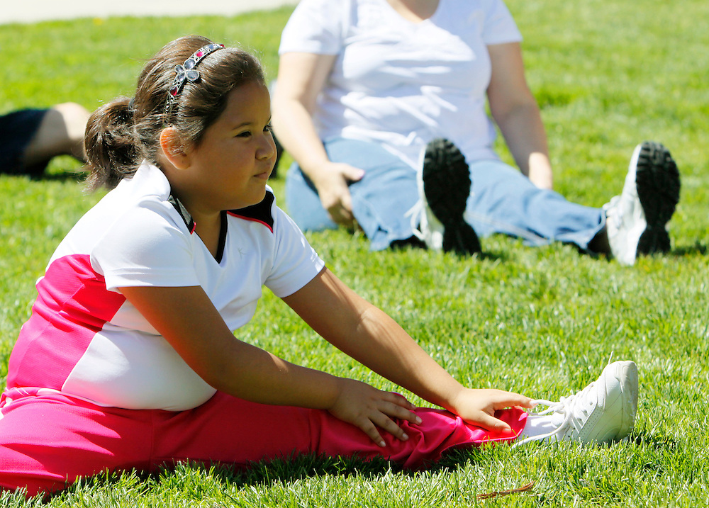 Fernanda Garcia-Villanueva, 8, stretches at a group exercise session in the 10-week Shapedown Program at The Children's Hospital in Aurora, Colorado May 29, 2010.  The program is part of the child and teen weight management program at the hospital. REUTERS/Rick Wilking (UNITED STATES)
