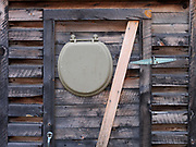Outhouse with toilet seat on door replacing the usual crescent moon, Fielding, Alaska.