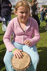 Young girl taking part in a drumming workshop at a Parklife summer activities event,