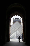 Person walking into the Louvre museum courtyard through one of the arched entrances