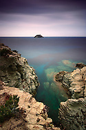 """The tiny Giraglia Isle with its lighthouse and Genovese watch tower stands out at sea in front of the rocky coast of the northern tip of the Cap Corse near to Barcaggio in Corsica, France. This wonderful part of the Corsica coast features countless spots like this, and it is easily accessible thanks to the """"sentier du douaniers"""", a track that links the village of Centuri to Macinaggio via Barcaggio, a path used in the past by the custom officers who surveyed the many small bays of the area..This picture was taken on a late afternoon of mid of September, and it's the result of 3 minutes of exposure obtained thanks to the use of a strong neutral filtration."""