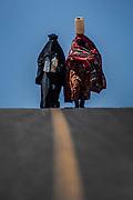 Donne risalgono il pendio con i contenitori dell'acqua il villaggio e la cittadella di Kawkaban.....Women coming back to the Kawkaban village with water...<br /> Yemen, January 2006.<br /> Photo Antonietta Baldassarre