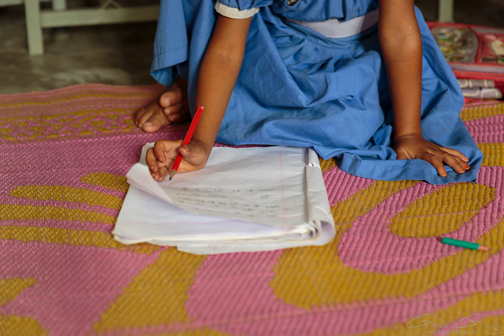 A girl writing in a notebook during a primary school class