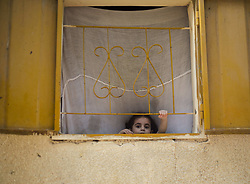 June 13, 2017 - Gaza City, The Gaza Strip, Palestine - A Palestinian refugee girl plays on the window of her family's temporary home in the Jabalya refugee camp in the northern Gaza Strip. (Credit Image: © Mahmoud Issa/Quds Net News via ZUMA Wire)