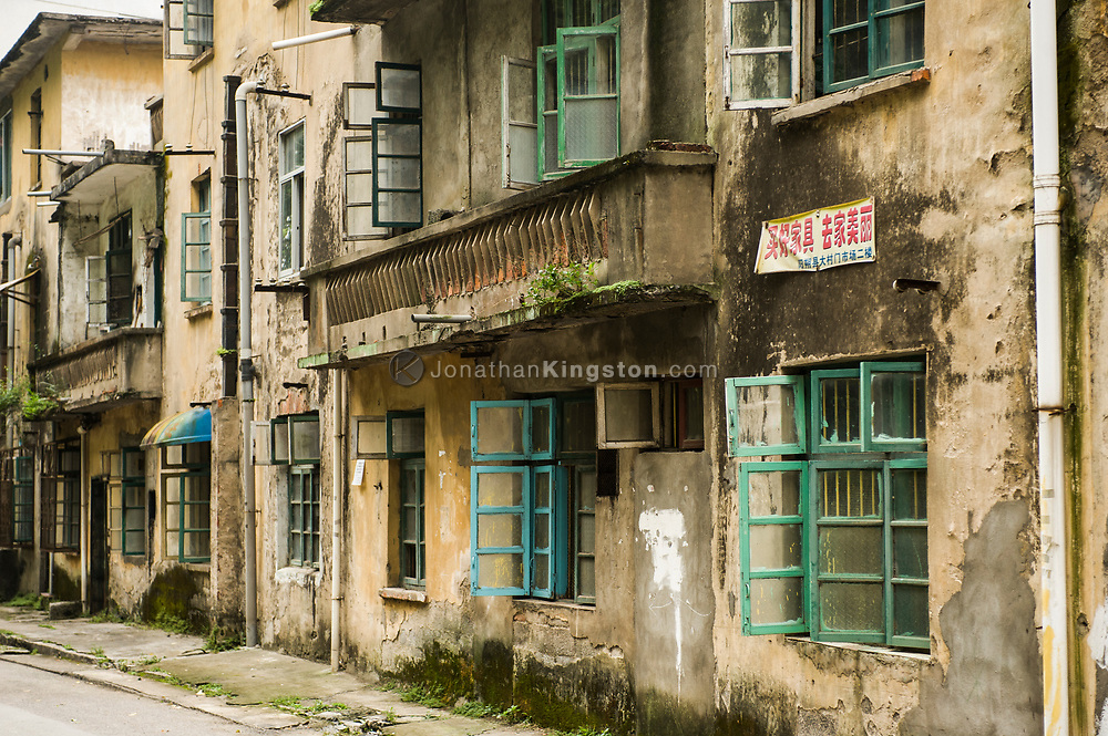 Dilapidated concrete building with colorful windows in Yangshuo, China.