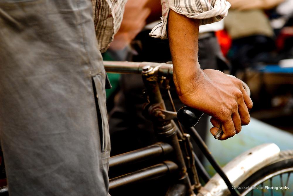 A close up of a rickshaw riders handlebars as he navigates the busy Delhi Streets, India