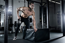 Muscular man performing one hand rowing exercise with kettlebell at the gym
