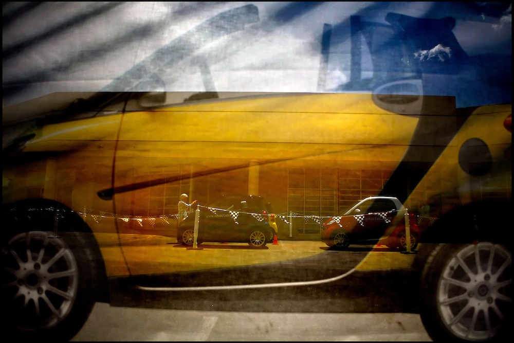 As seen through a promotional screen, a potential customer inspects the 2008 Smart Fortwo car at Garcia Infiniti. The tiny, two-seat European imports will be available for sale in the United States next year.
