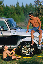 Boy having a good laugh while spraying water at a shirtless man sitting on a truck