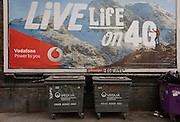 Vodafone mountains ad for 4G network services and dystopian refuse bins in south London.