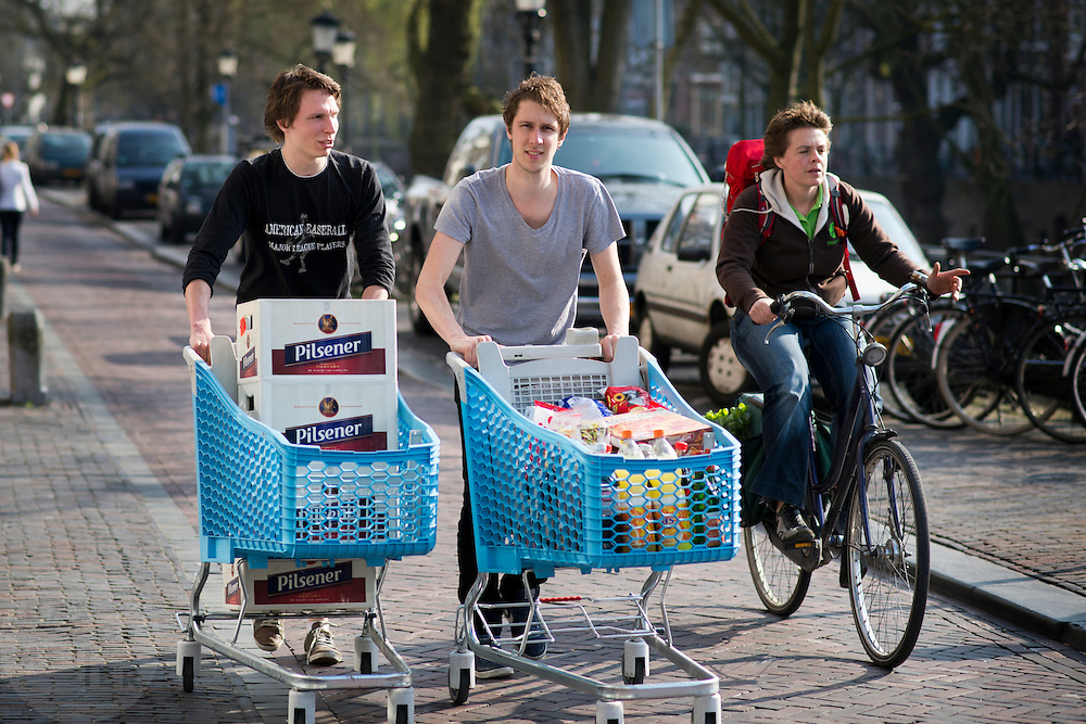 Twee studenten lopen met twee volle winkelwagens van de Albert Heijn met drinken door het centrum van Utrecht.<br />