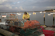 Fisherman mending lobster pots. Small fishing and sailing hamlet of Felixstowe Ferry at the mouth of the River Deben, Suffolk, England