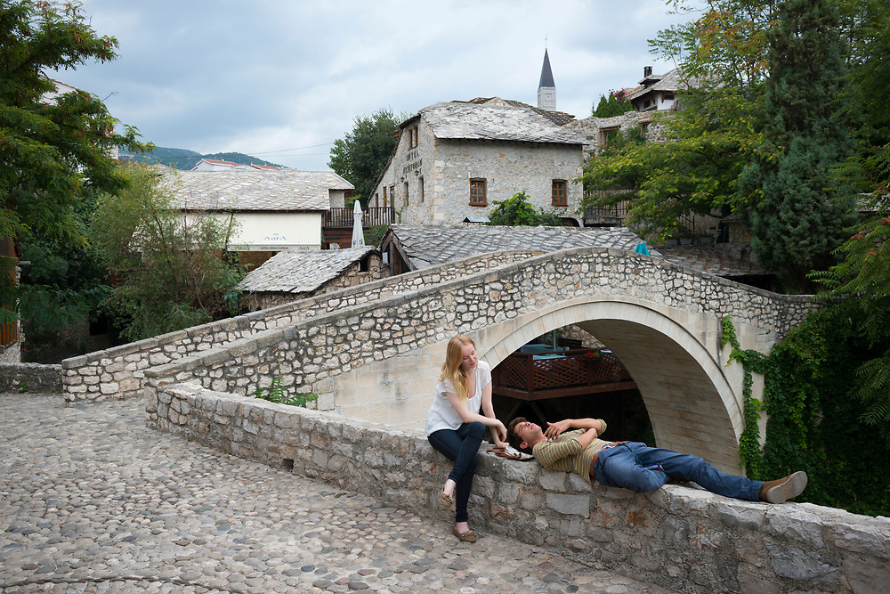 Two young adults, a woman from Finland and a man from Italy, relax in conversation beside the historic Crooked Bridge in Mostar, Bosnia and Herzegovina.