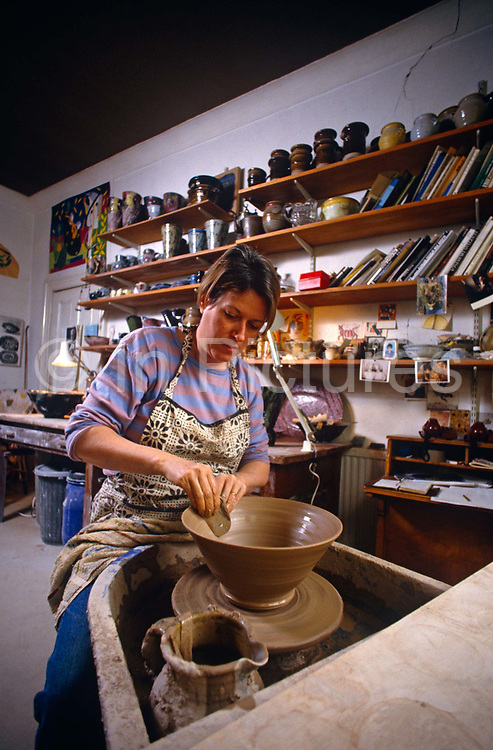 The artist Janice Tchalenko throws a pot in her home studio in south London. With past creation on shelves behind, she smooths the sides of a vessel as it turns on the wheel. Tchalenko studied at Putney School of Art and Harrow School of Art then taught at Camberwell School of Art. She specialized in undecorated domestic stoneware and developed a reputation as a highly competent thrower. In the late 1970s she discovered she also had a talent for decoration and started making high-fired stoneware with bright and colourful designs. She became a tutor at the Royal College of Art in 1981 and this was shortly followed by two exhibitions - one with John Hinchcliffe the textile designer and the other as a one-woman show at the Blum Helman Gallery in New York - that established her as one of the top British potters.