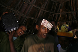 Guests place money on the head of groom Manale Bihone, 23, during his wedding celebration to Alemenesh Bere, 11, in the Yeterater Miriam village outside of Bahir Dar, Amhara Region, Ethiopia on May 26, 2007.  Because many married adolescents are pulled out of school at an early age, they may be unfamiliar with basic reproductive health issues, including the risk of HIV. Married adolescents often face familial and societal expectations to have children as soon as they are married. Even if contraceptive services are available, married adolescent girls may lack the power to use them, aggravating the risks of maternal mortality and morbidity for pregnant adolescents.