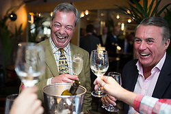 LNP HIGHLIGHTS OF THE WEEK 25/04/14 © Licensed to London News Pictures . 24/04/2014 . Knutsford , UK . UKIP leader NIGEL FARAGE on a walkabout tour of Knutsford on the European election campaign trail , shares a drink with customers in a wine bar . Farage has come under fire in recent days over a controversial UKIP billboard campaign . Photo credit : Joel Goodman/LNP