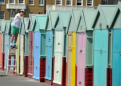 © licensed to London News Pictures. BRIGHTON  UK. 21/04/11.A  man paints a beach hut on Hove seafront. People flock to Brighton Beach today (21 April 11) to catch the sunshine before the start of the Easter Bank Holiday in Britain. Temperatures are set to continue to rise over the weekend. Photo credit should read Stephen Simpson/LNP