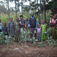 Jumanne Abdallah's family in their kitchen garden on his farm in Tarime, Mara, Tanzania. Dolca carries her baby brother. Mr Abdallah has planted 1,700,000 trees, mainly Eucalyptus and Grevillea but also leguminous species for firewood, forage and nitrogen-fixing green manure.