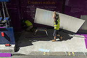 A construction site workman carries reflective metal sheeting on to the site of a development on Victoria Street in Westminster, on 30th July 2020, in London, England.