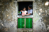 Philippines, Batanes. Girl from Sabtang Island at the window of her house in a little village.