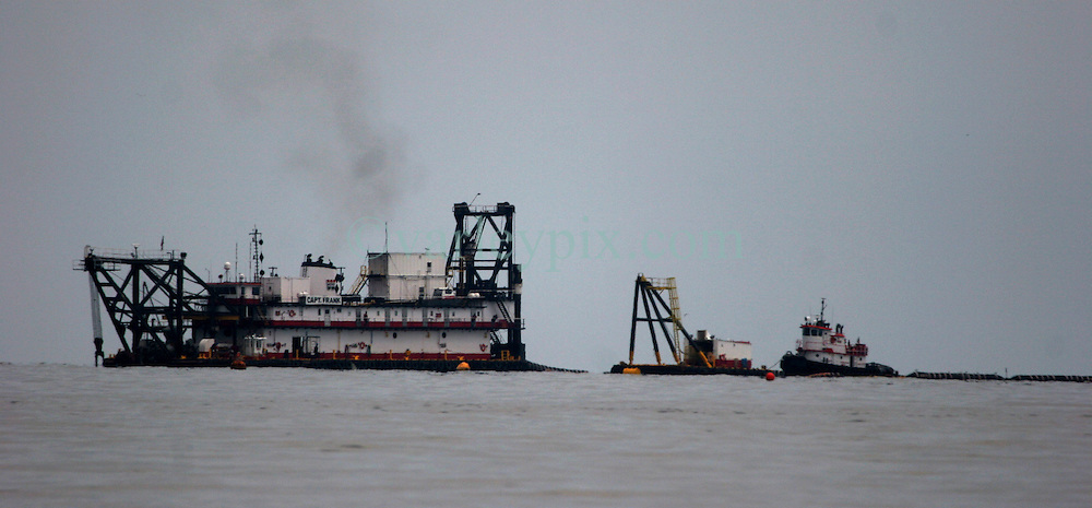 26 May 2010. Barataria Bay, Louisiana. <br /> Dredging operations begin just off the coast of Grande Terre Island near Gand Isle as local authorities prepare to build up the marsh land to protect the coast from further oil penetration. The environmental and economic impact is devastating with many shrimp boats tied up, vacation rentals and charter boat fishing trips cancelled the only business for shrimpers is loading and laying boom and working for big oil. Oil from the Deepwater Horizon catastrophe is evading booms laid out to stop it thanks in part to the dispersants which means the oil travels at every depth of the Gulf and washes ashore wherever the current carries it. <br /> Photo credit; Charlie Varley<br /> www.varleypix.com