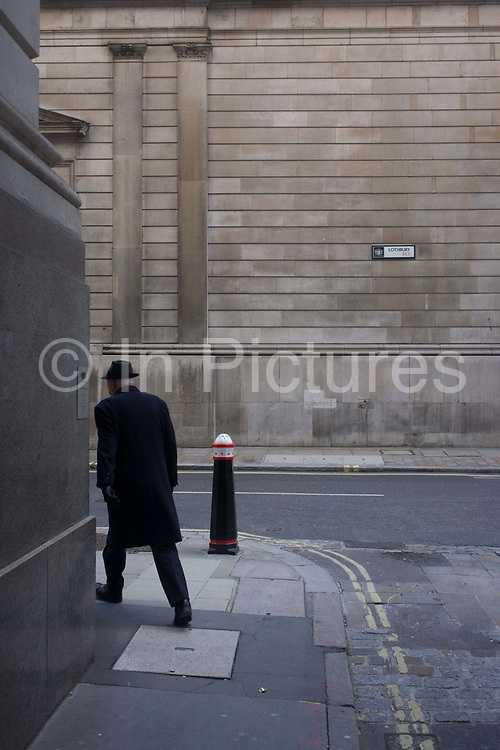 A striding businessman turns the corner of Lothbury and Tokenhouse Yard, two narrow and historic streets with the high walls of the Bank of England in the background - in the City of London, the capital's financial district. The area was populated with coppersmiths in the Middle Ages before later becoming home to a number of merchants and bankers. Lothbury borders the Bank of England on the building's northern side. Tokenhouse St dates from Charles I and was where farthing tokens were coined. The City of London is the capital's historic centre first occupied by the Romans then expanded during following centuries until today, it has a resident population of under 10,000 but a daily working population of 311,000.