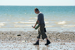 © Licensed to London News Pictures. 03/07/2014. Bognor Regis, UK. A man uses a metal detector as the tide recedes.  People enjoy the hot sunny weather at the seaside resort of Bognor Regis today 3rd July 2014. Forecasters are predicting it to be the hottest day of 2014 so far. Photo credit : Stephen Simpson/LNP