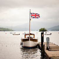 A boat with a Union Jack flag moored on a lake pier in the Lake District, UK