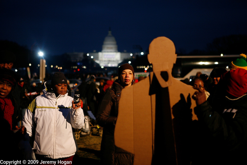 Barack Obama supporters gathered on the National Mall are photographed with a card board cutout of the future president on the evening before Obama's inauguration ceremony at the Capitol Building.