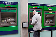 A man makes a withdrawl. The Lloyds TSB cashpoint ATM machines.