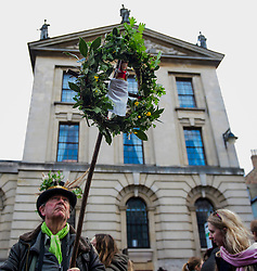 © Licensed to London News Pictures. 01/05/2017. Oxford, UK. A man holds up a pagan wreath as Oxford University students and members of the public celebrate May Day in the early hours of the morning near Magdalen Bridge in Oxford, Oxfordshire. Students were again prevented from jumping from the bridge in tot he water, which has historically been a tradition, due to injuries at a previous years event . Photo credit: Ben Cawthra/LNP