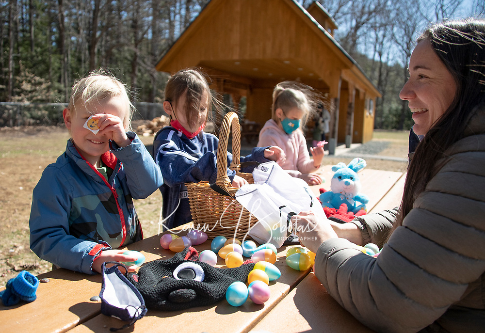 Ian, Vivian and Evelyn Tyler open up their Easter eggs collected during the Egg Hunt and Story Walk through Gilford's Nature Trail Saturday morning.  (Karen Bobotas Photo/for The Laconia Daily Sun)