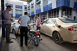 © Licensed to London News Pictures. 26/06/2014. Sulaimaniyah, Iraq. Iraqi drivers fill their tanks at a petrol station in Sulaimaniyah, Iraqi-Kurdistan. Despite being an oil-rich country Iraq's main oil refinery at Baiji is now the hands of ISIS insurgents cutting much of the fuel to the rest of the country. Petrol rationing has come in to force across northern Iraq with huge queues that mean many drivers wait in line for hours, sometimes overnight, just to receive their allowance of 30 litres. The shortage has also seen a huge increase in fuel prices with a litre of petrol rising 150% from 500 Iraqi Dinars to 1500 Iraqi Dinars. Photo credit: Matt Cetti-Roberts/LNP