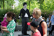 Charlie Chaplin street performer George, dressed up as The Tramp character, poses with tourists to have the picture taken on the Southbank walkway. The South Bank is a significant arts and entertainment district, and home to an endless list of activities for Londoners, visitors and tourists alike.