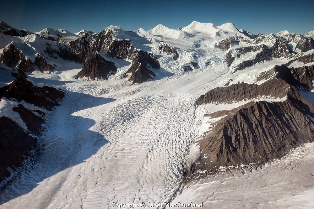 This image is looking up a glacier in the Denali mountain range on a sunny afternoon fly over.