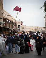 People walk on a winter afternoon through the popular pedestrian area of Souk Waqif in Doha, Qatar (February 2017).