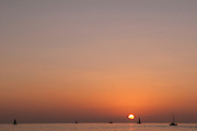 The sun sets behind silhouetted sailboats.