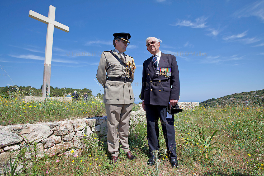 Mcc0031516 . Daily Telegraph..Flight Lieutenant Freddie Nicoll DFC talks with DA Lt Col Phil Osment after laying a wreath at an RAF memorial (cross in background is for the Croatian War of Independence 1991-1995)  on the island of Vis, Croatia .. A reunion of British WW2 Veterans, probably for the last time. They are some of the last survivors of an Allied combined garrison of Royal Navy, Royal Marine Commandos, Army and Royal Air Force personnel who took over the Island in 1943 and held it until the end of the War. From here they harried Axis Forces in what was Yugoslavia, providing supply drops to the Partisans and, at one point, refuge for Marshall Tito when he was nearly captured by German Forces .