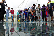 ZHANGJIAJIE, CHINA - JUNE 25:<br /> <br /> A visitor strikes the glass-bottomed bridge with a hammer for a safety test at Zhangjiajie Grand Canyon on June 25, 2016 in Zhangjiajie, Hunan Province of China. World\'s tallest and longest glass-bottomed bridge has been completed and took a global broadcast through television and internet medias to show its safety. More than thirty citizens and visitors thumped the bridge with hammer in the test event.<br /> ©Exclusivepix Media