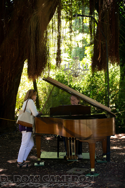 An unidentified man plays for an audience of one, at the fifth annual Flower Piano exhibition at the San Francisco Botanical Garden in Golden Gate Park, Friday, July 19, 2019 in San Francisco. The exhibition continues through Monday. (Photo by D. Ross Cameron)