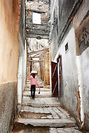 A girl, carrying a plate with a dough on her head, walks in a narrow lane in the old town (medina) of Fés, Morocco.