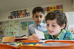 Schoolboys reading a message in classroom, Munich, Bavaria, Germany