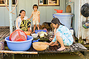 13 MARCH 2006 - CHAU DOC, AN GIANG, VIETNAM: A family does their dishes on a houseboat in a village near Chau Doc, Vietnam in the Mekong delta. The Mekong is the lifeblood of southern Vietnam. It is the country's rice bowl and has enabled Vietnam to become the second leading rice exporting country in the world (after Thailand). The Mekong delta also carries commercial and passenger traffic throughout the region.  Photo by Jack Kurtz