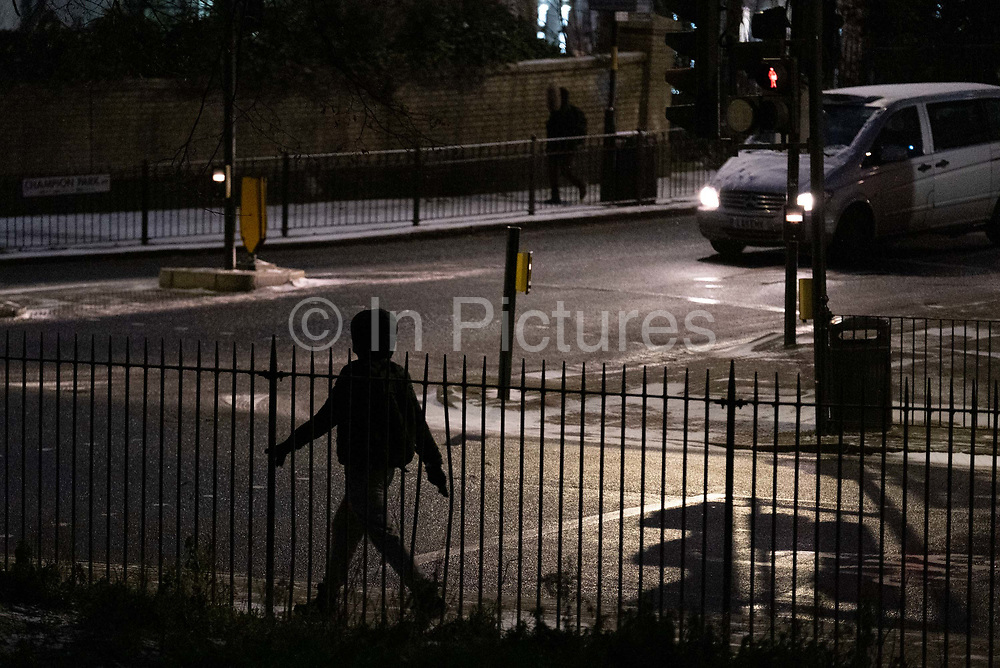 The silhouette of a striding pedestrian makes their way on a winter morning towards their destination, across the road on Denmark Hill in south London, on 8th February 2021, in London, England.