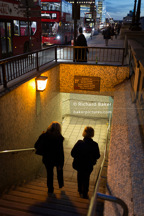 Two women descend steps into the tunnel under London Bridge during the evening rush-hour, on 8th November 2018, in London, England.