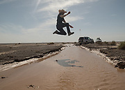 The archeologist jumps over a seasonal river.
