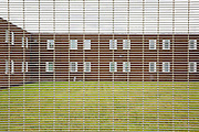 A two story wing through a security fence inside HMP Featherstone, Wolverhampton, Staffordshire United Kingdom. HMP Featherstone is a Category C adult male training prison with a population of around 700 and operated by HM Prison Services. (Picture credit: © Andy Aitchison)